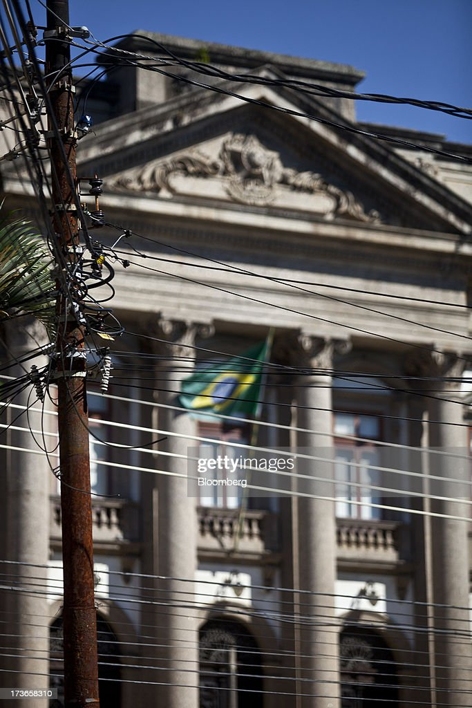Telecommunication and electricity cables run between poles in front of a building displaying a Brazilian flag in Rio de Janeiro, Brazil, on Monday, July 15, 2013. Energy developers in Brazil will bid for contracts to sell electricity Dec. 13 from plants due to go into operation in five years, including a 700-megawatt hydropower project in the Amazon. Photographer: Dado Galdieri/Bloomberg via Getty Images