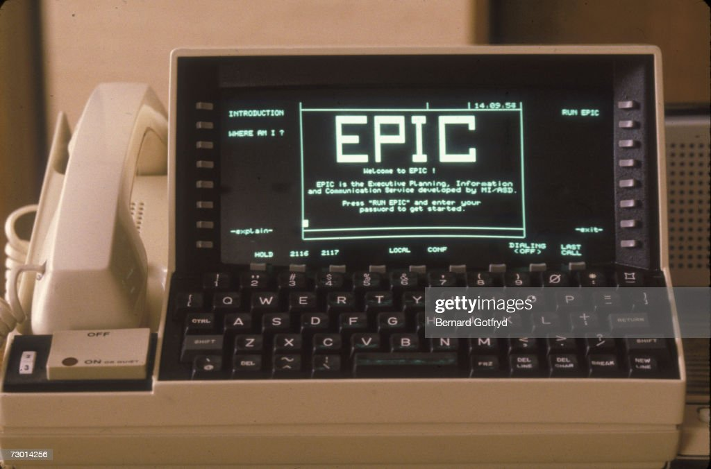 A telecommunications device for the office is seen on a desk at Bell Telephone Laboratories, New Jersey, late 1970s or early 1980s. The device, which consists of a telephone handset, a Qwerty keyboard, a small CRT desiplay screen, and a large on/off button, describes it self as 'EPIC' for 'Executive Planning Information and Communication service' and is most likely a kind of intercom.