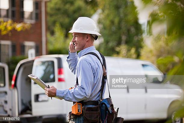 Telecommunications installer using work order at his truck and talking on a cell phone