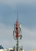 Telecommunications metal tower against blue sky clouds