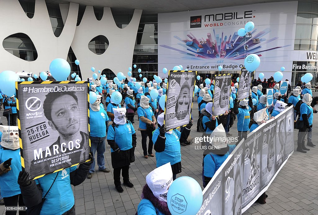 Telefonica's workers, with bags over their heads, protest against layoffs outside the 2013 Mobile World Congress in Barcelona on February 25, 2013. The 2013 Mobile World Congress, the world's biggest mobile fair, is held from February 25 to 28 in Barcelona. The placard reads: 'Marcos, 25 years as operator for Telefonica/Movistar, fired for being ill.'