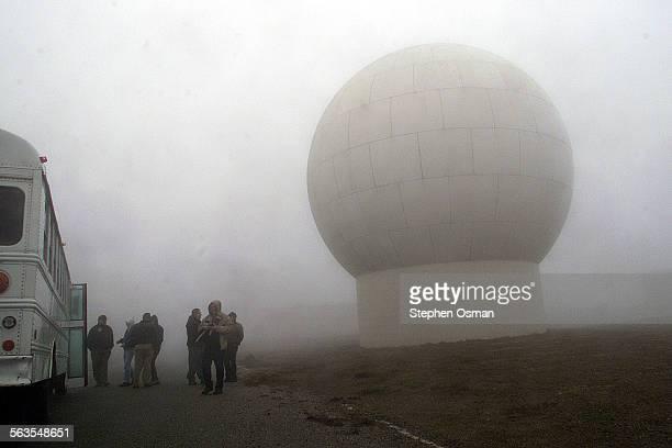 A telemetry receiving antennae dwarfs visitors to San Nicolas Island Navy officials took members of the media to San Nicolas Island for a day of show...