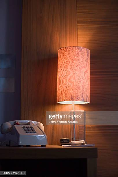 Telephone and illuminated lamp on bedside table