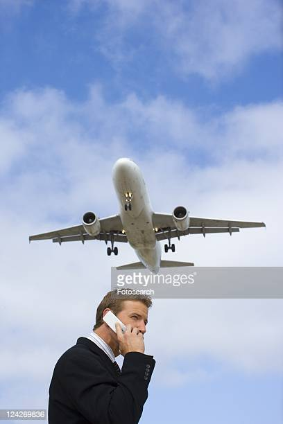 A Telephone Calling Businessman with a Airplane in the Background, Low Angle View, Waist Up