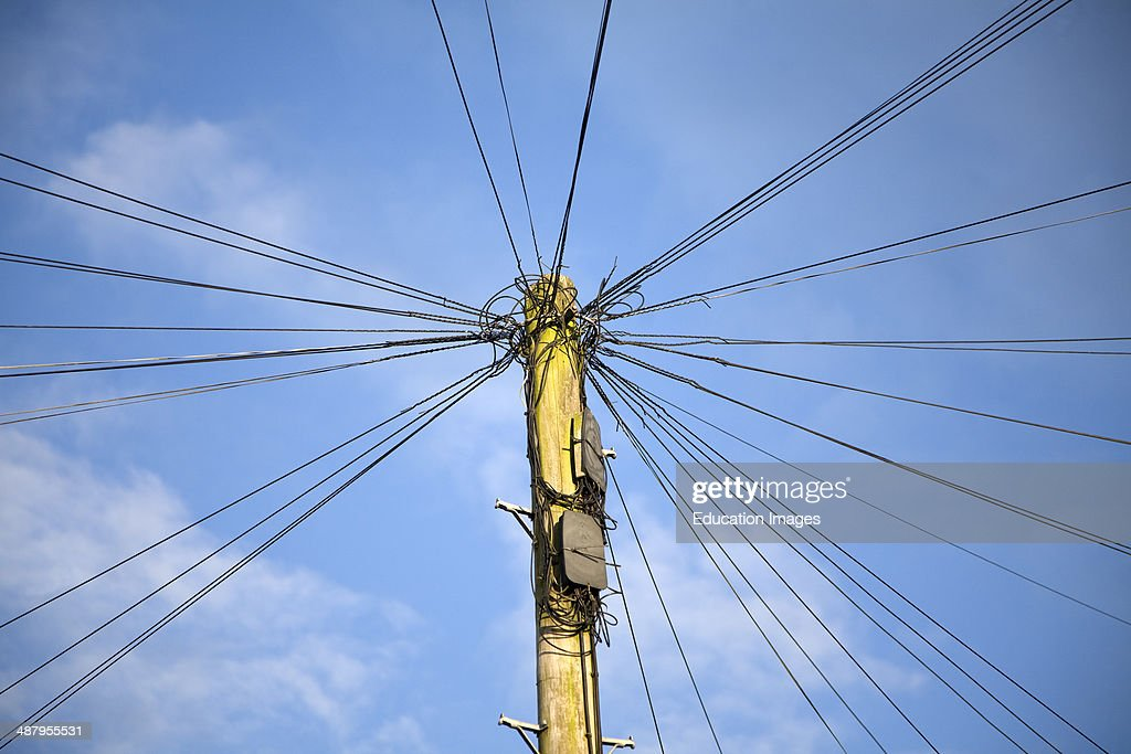 Telephone line cables radiating out fro telegraph pole against blue sky UK