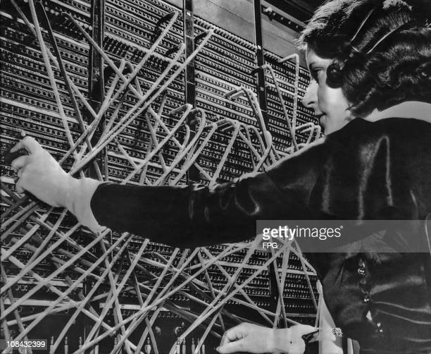 A telephone operator putting through a call at a switchboard circa 1930