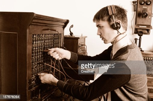 Telephone operator using antique switchboard