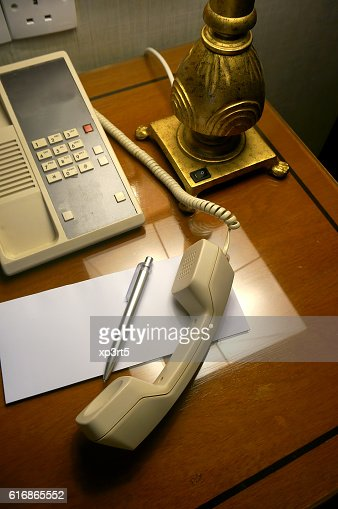 Telephone, pen and blank white paper on hotel room : Stock Photo