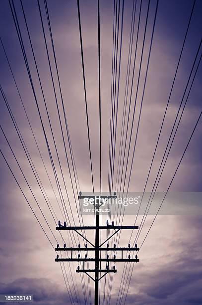 A telephone pole and lines across a purple clouded sky