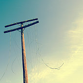 Telephone pole with severed cables, low angle view (cross-processed)
