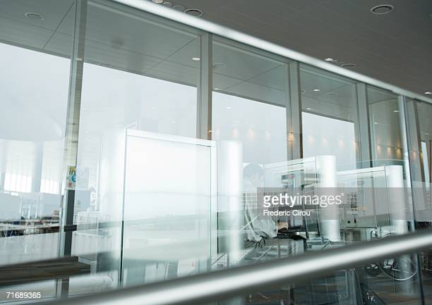 Telephones in airport, seen through glass wall