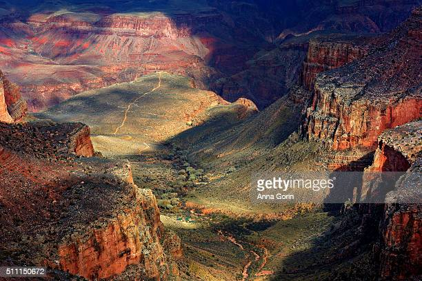 Telephoto view of Bright Angel trail leading through valley in Grand Canyon South Rim, dramatic winter light