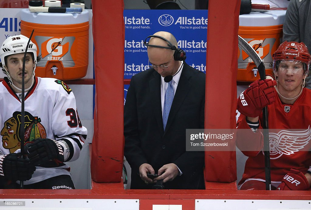 Television analyst Pierre McGuire checks his phone as Dave Bolland #36 of the Chicago Blackhawks and Justin Abdelkader #8 of the Detroit Red Wings look on from the bench during an NHL game at Joe Louis Arena on March 31, 2013 in Detroit, Michigan.