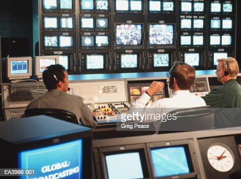 Television broadcast control room with director and crew