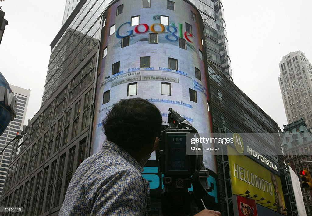 A television camera man video tapes a sign marking Google being traded on the NASDAQ Marketsite August 19, 2004 in New York City. Shares of Google Inc. were expected to begin trading publicly on the Nasdaq Stock Market August 19, at a lower per share price than anticipated.