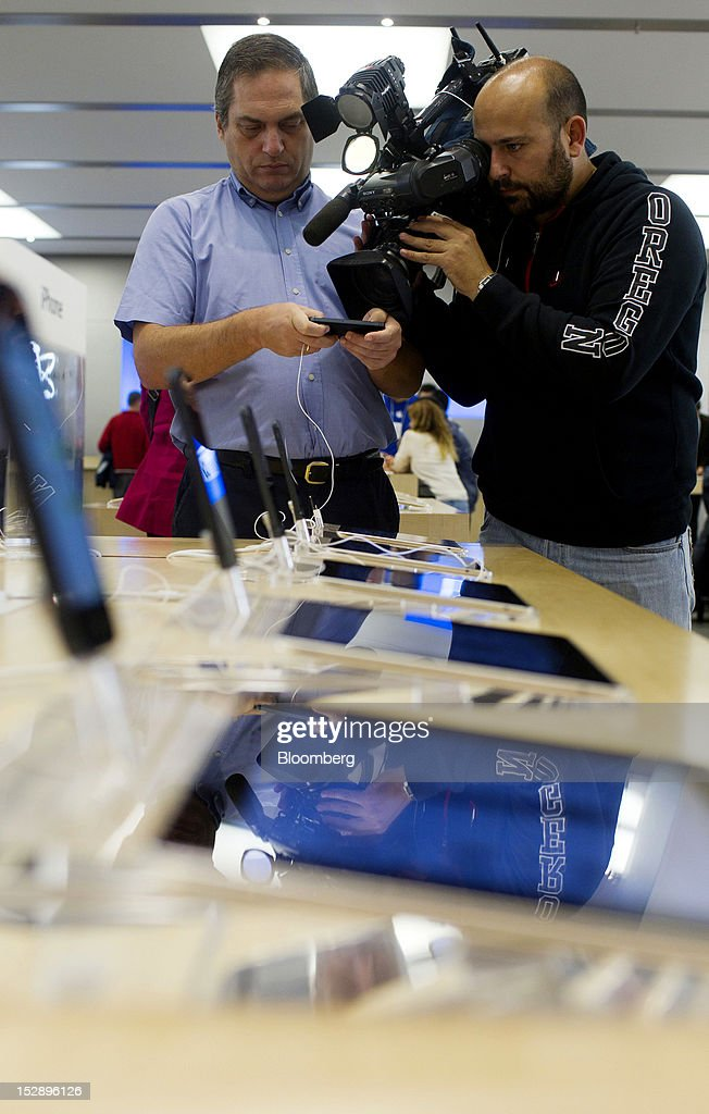 A television camera operator films a customer as he holds his new Apple Inc. iPhone 5 inside the Apple store in the Gran Plaza 2 shopping mall in Majadahonda, near Madrid, Spain, on Friday, Sept. 28, 2012. Apple said it is working to catch up with demand, 'We are working hard to get an iPhone 5 into the hands of every customer who wants one as quickly as possible,' Apple Chief Executive Officer Tim Cook said in a statement. Photographer: Angel Navarrete/Bloomberg via Getty Images
