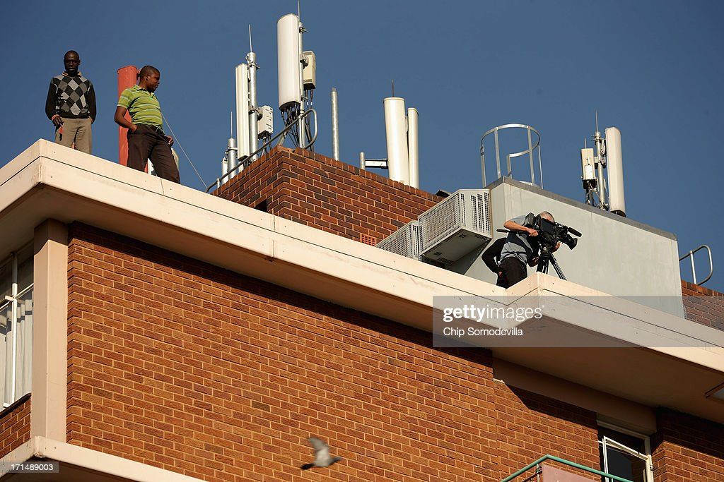 A television camera operator records from the rooftop of the highrise apartments across the street from the Mediclinic Heart Hospital where former South African President Nelson Mandela is being treated June 25, 2013 in Pretoria, South Africa. South African President Jacob Zuma confirmed on June 23 that Mandela's condition has become critical since he was admitted to the hospital over two weeks ago for a recurring lung infection.