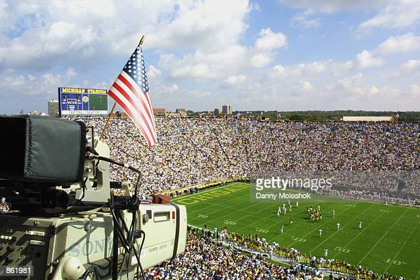 A television camera with an American Flag documents the NCAA football game between the Western Michigan Broncos and the Michigan Wolverines on...