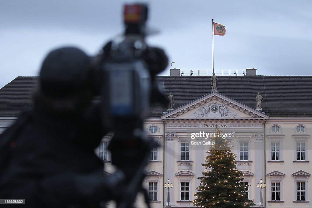 A television cameraman films Schloss Bellevue presidential palace on January 3, 2012 in Berlin, Germany. German President Christian Wulff is coming under increasing pressure to resign following reports that he personally called Editor-in-Chief Kai Diekmann of Bild Zeitung and threatened him should the paper publish a story about Wulff's personal finance conduct while Wulff was prime minister of Lower Saxony.