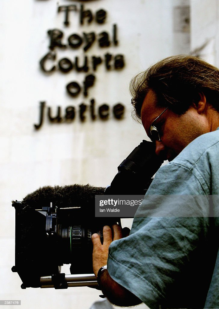 A television cameraman films witnesses arriving at the Royal Courts of Justice to give evidence at the Hutton inquiry August 11 2003 in London...