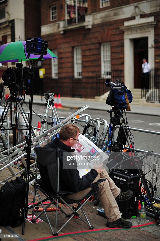 A television cameraman reads a newspaper as he waits outside the Lindo Wing of Saint Mary's Hospital in London, on July 12, 2013. Prince William and his wife Catherine's baby, which will be third in line to the throne, will be born in the private Lindo wing of St Mary's Hospital, where William was born in 1982 and his brother Harry in 1984.