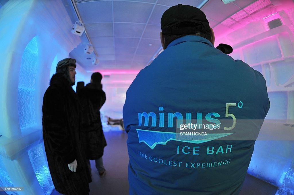 A television cameraman wears a parka in the Minus 5 Ice Bar during a preview at the New York Hilton Midtown Hotel July 9, 2013 in New York. The bar is constructed of 90 tons of ice and is kept at a temperature of -5 degrees C (23 degrees F). Guests are given parkas, gloves and hats and for an additional fee, fur coats. Designs in the wall and around the bar are carved by ice sculptor Peter Slavin. AFP PHOTO/Stan HONDA