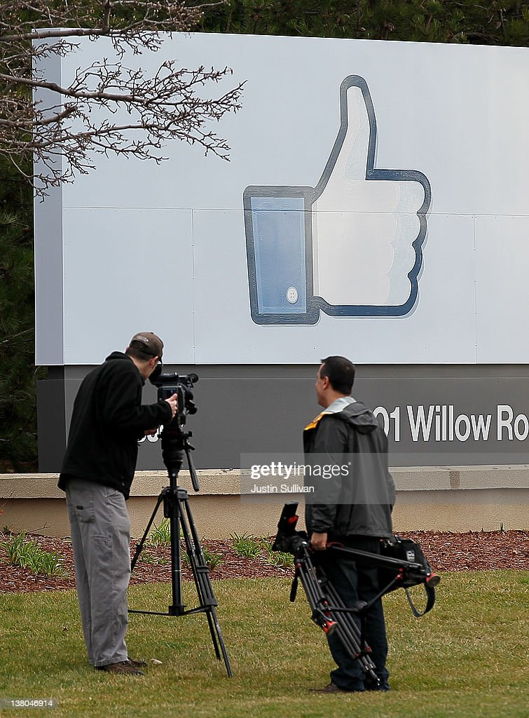 Television cameramen videotape a sign posted in front of the Facebook headquarters on February 1, 2012 in Menlo Park, California. Facebook is expected to file for its first initial public offering today seeking to raise at least $5 billion.