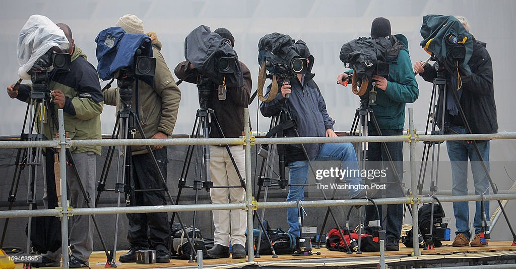 Television cameras and their operators bundled up against a foggy mist during rehearsal for the upcoming inauguration of President Barack Obama on January, 13, 2013 in Washington, DC.