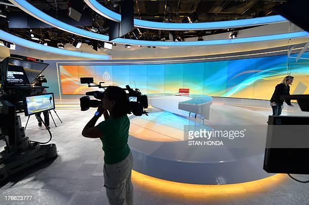 A television camerawoman takes video of the new Al Jazeera America television broadcast studio on West 34th Street August 16 2013 in New York Al...