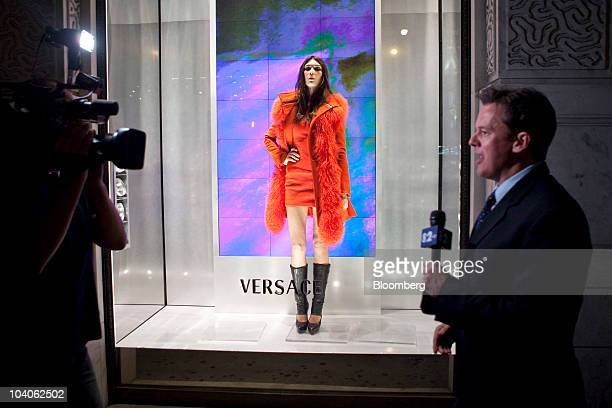 A television crew films next to a live model in a window display at the Versace store on Fifth Avenue during the second annual Fashion's Night Out in...