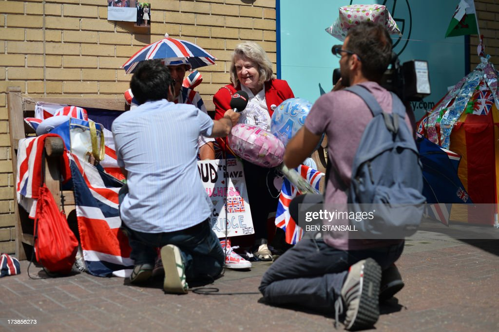 A television crew interview a royal supporter outside the Lindo Wing of St Mary's Hospital in London, on July 18, 2013, where Prince William and his wife Catherine's baby is expected to be born. The long wait for the birth of Britain's royal baby is record business for bookmakers, as punters worldwide bet on a girl called Alexandra to be born any day now.