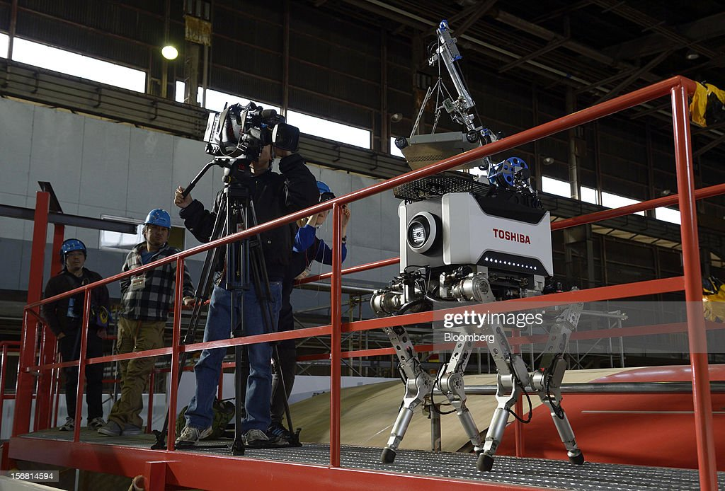 A television crew member films a Toshiba Corp. tetrapod robot walking along a catwalk at the company's Yokohama Complex in Yokohama City, Kanagawa Prefecture, Japan, on Wednesday, Nov. 21, 2012. Toshiba's new robot was developed to work in areas too dangerous for humans. Photographer: Akio Kon/Bloomberg via Getty Images