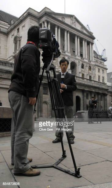 Television crews broadcast from outside the Bank of England in London which today cut interest rates by 15% in its most dramatic attempt yet to...