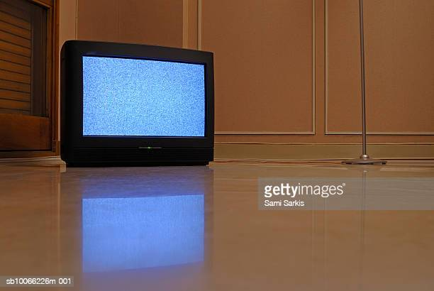 Television displaying static reflected in floor