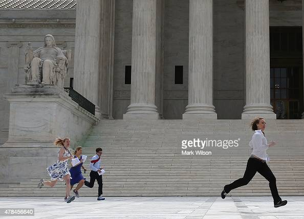 Television interns run to their reporters stationed outside after being handed the ruling on the Affordable Care Act at the US Supreme Court June 25...