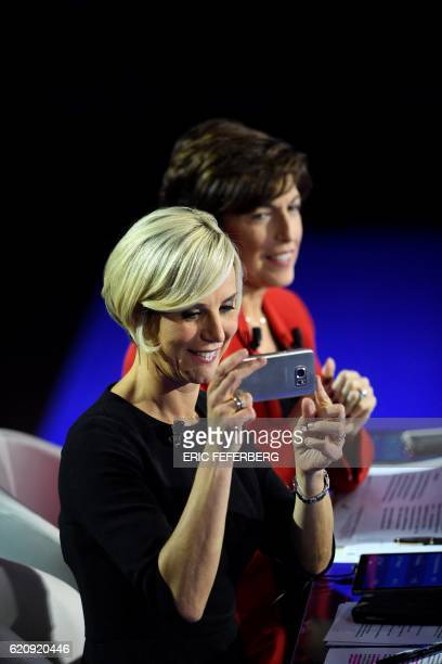 Television journalist Laurence Ferrari takes a photo with her mobile phone as fellow journalist Ruth Elkrief looks on during an interruption of the...