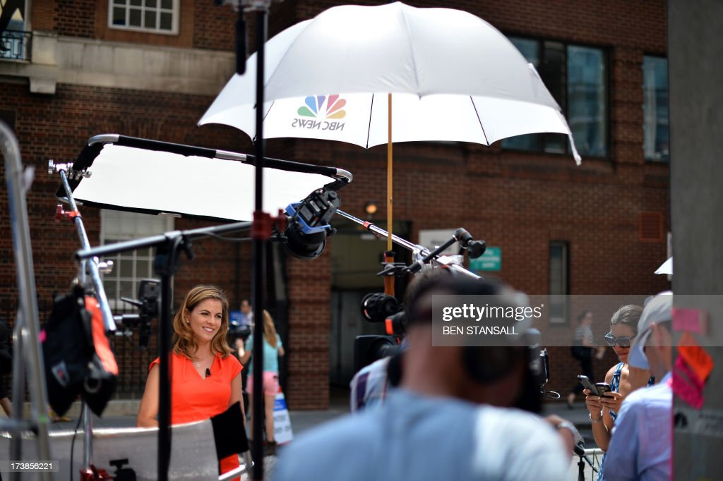 A television journalist (L) prepares to record a piece to camera outside the Lindo Wing of St Mary's Hospital in London, on July 18, 2013, where Prince William and his wife Catherine's baby is expected to be born. The long wait for the birth of Britain's royal baby is record business for bookmakers, as punters worldwide bet on a girl called Alexandra to be born any day now.