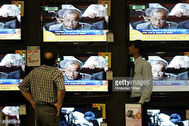 Television News Channel A Man watches Finance minister Pranab Mukherjee presented the interim budget on TV Screens on a TV Showroom