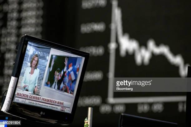 A television news report shows France's presidentelect Emmanuel Macron as the DAX index curve is displayed beyond inside the Frankfurt Stock Exchange...
