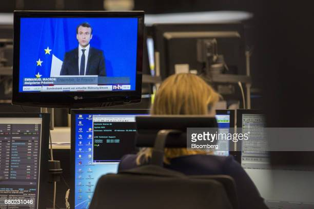 A television news report shows Presidentelect Emmanuel Macron speaking as a trader monitors financial data inside the Frankfurt Stock Exchange in...