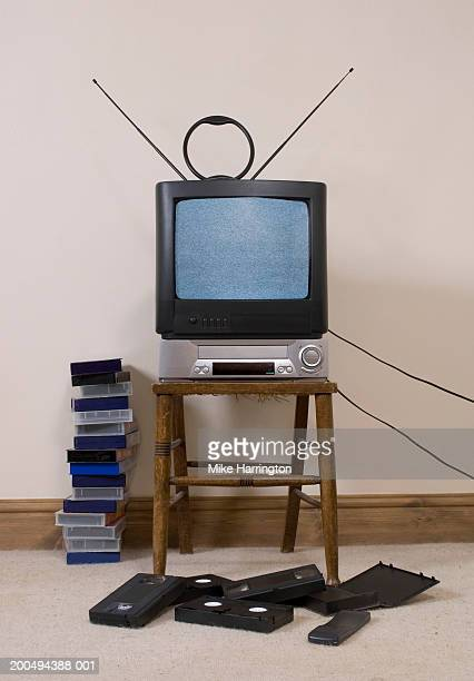 Television on stool, screen showing static, video cassettes on floor
