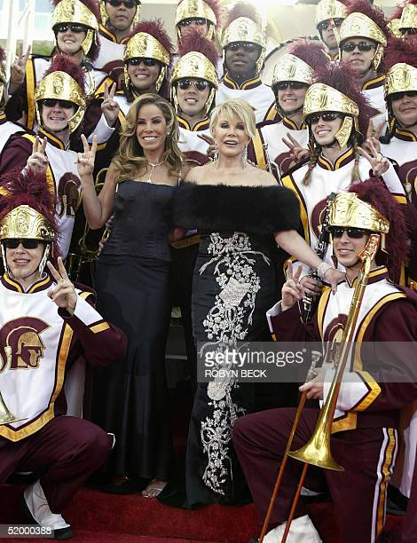 US television personalities Joan and Melissa Rivers pose for a photo with the USC marching band on the red carpet before the start of the 62nd annual...