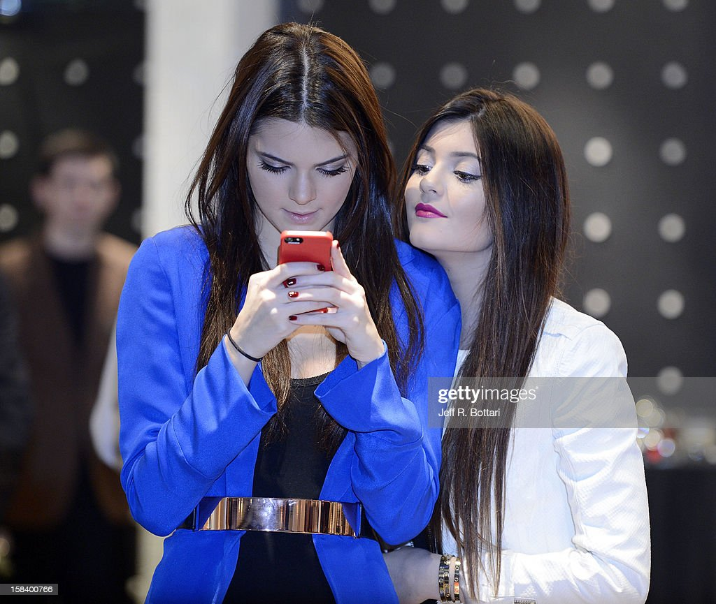 Television personalities Kendall Jenner (L) and Kylie Jenner look at photos on their phones after taking pictures of the crowd as they appear at the Kardashian Khaos store at The Mirage Hotel & Casino for a fan meet-n-greet on December 15, 2012 in Las Vegas, Nevada.