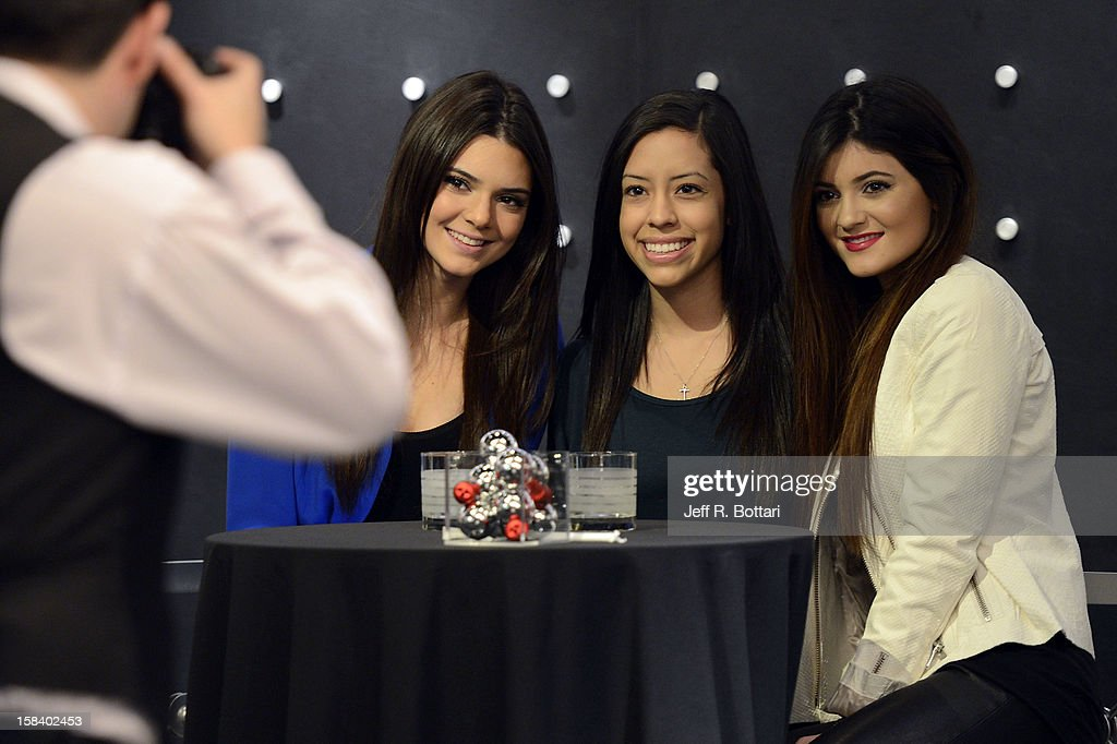 Television personalities Kendall Jenner (L) and Kylie Jenner (R) meet with a fan (C) and pose for photographs at the Kardashian Khaos store at The Mirage Hotel & Casino for a fan meet-n-greet on December 15, 2012 in Las Vegas, Nevada.