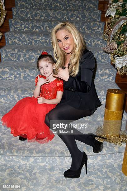 Television personality Adrienne Maloof poses for a photo with a guest at Adrienne Maloof's Annual Holiday Party with Never Too Hungover on December...