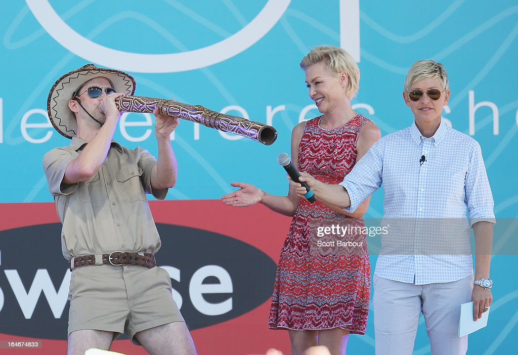 Television personality Ellen DeGeneres (R) and her wife Portia de Rossi watch as executive producer Andy Lassner plays a didgeridoo on stage during the filming of her television show at Birrarung Marr on March 26, 2013 in Melbourne, Australia. DeGeneres is in Australia to film segments for her TV show, 'Ellen'.