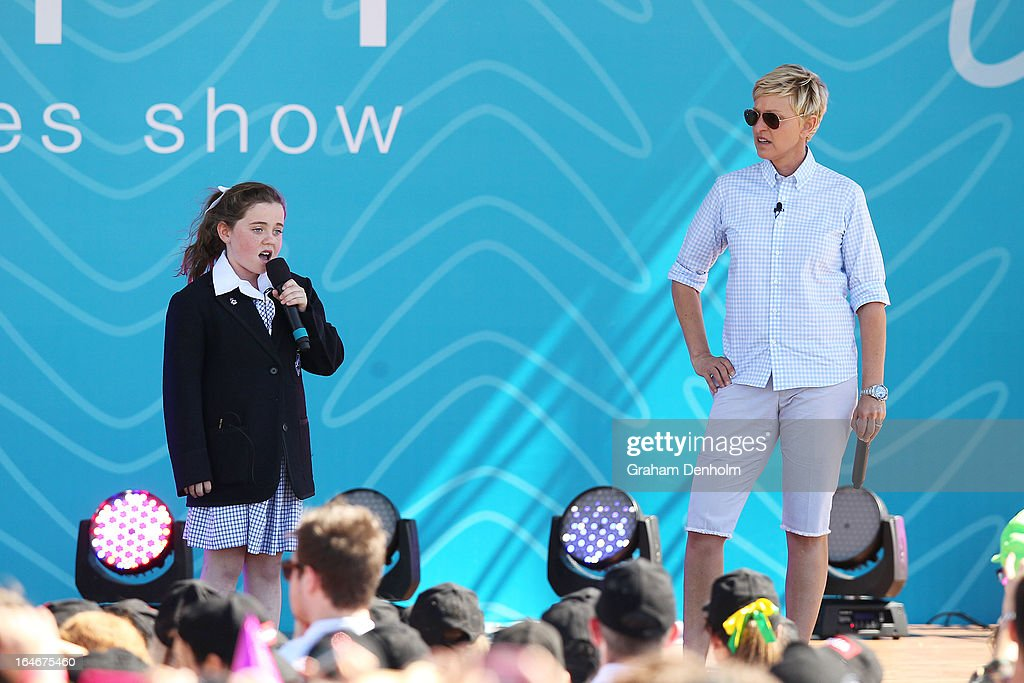 Television personality Ellen DeGeneres (R) appears on stage as schoolgirl Georgia Perry sings during the filming of DeGeneres' television show at Birrarung Marr on March 26, 2013 in Melbourne, Australia. DeGeneres is in Australia to film segments for her TV show, 'Ellen'.