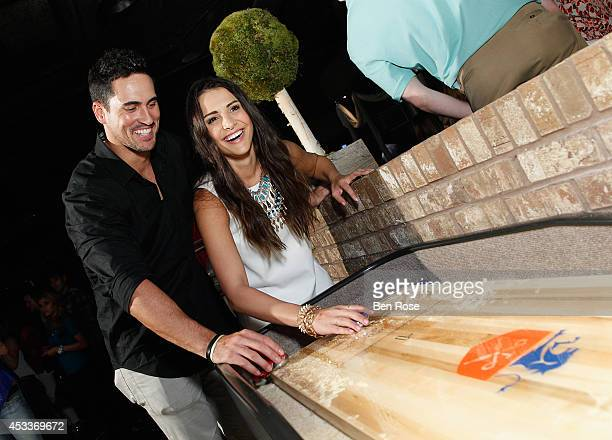 Television personality Josh Murray and television personality Andi Dorfman play shuffleboard during a surprise birthday party for Josh Murray thrown...