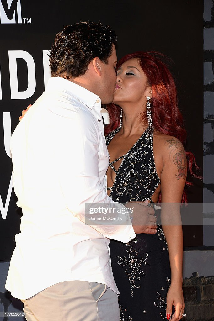Television personality Nicole 'Snooki' Polizzi (Detail: NYC Glitz dress) (R) with husband Jionni LaValle (L) attend the 2013 MTV Video Music Awards at the Barclays Center on August 25, 2013 in the Brooklyn borough of New York City.