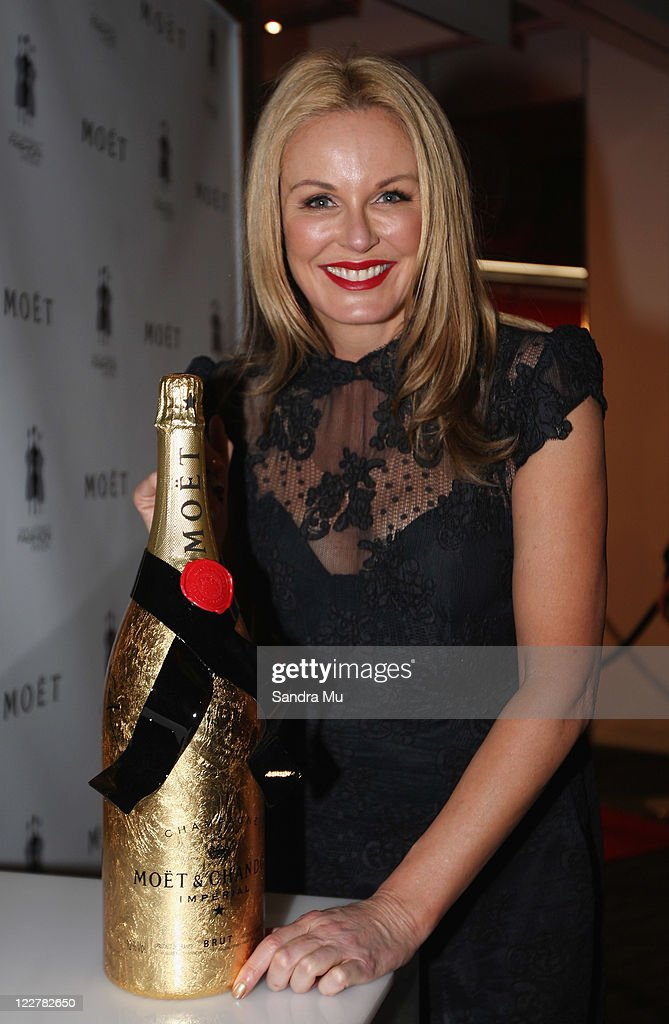 Television presenter Charlotte Dawson signs a gold bottle of Moet at the Moet Party marking the start of New Zealand Fashion Week 2011 at Viaduct...